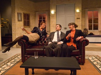 Suzette (Rhiannon Leach) introduces herself to Jacqueline (Cat Jardine) much to the discomfort of Robert (Mark Briggs).
